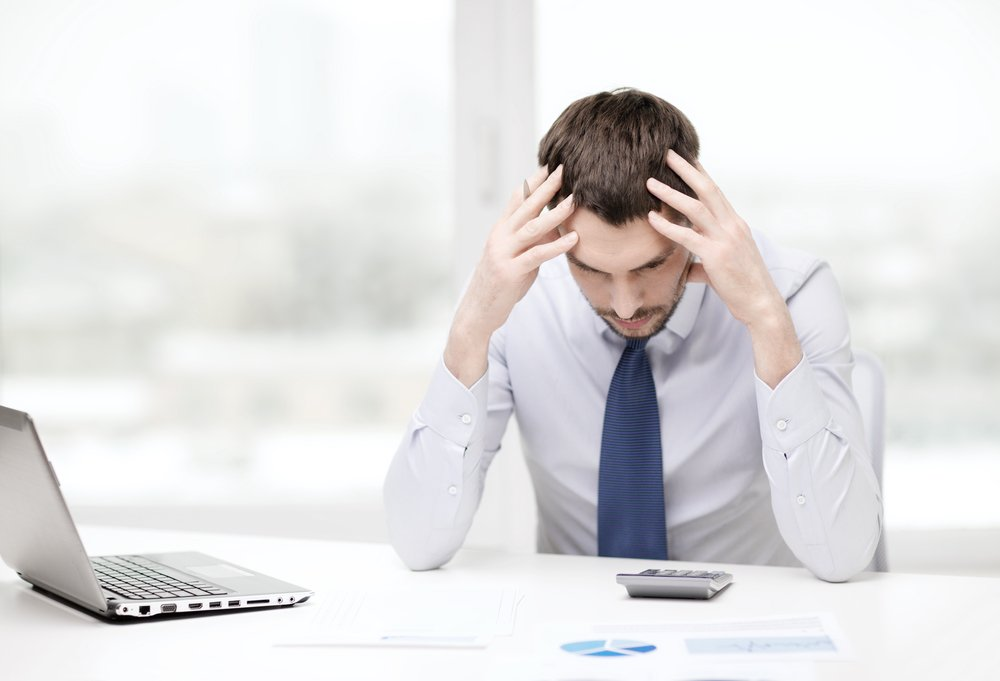 Stressed out businessman at desk. Biggest tax mistakes made by small businesses